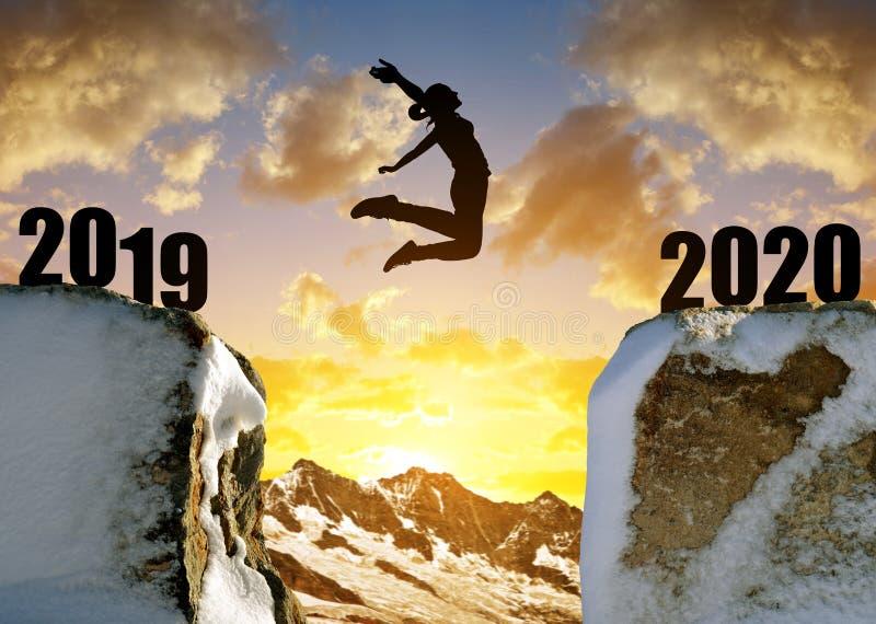 现出轮廓女孩跳跃到新年2020年 库存照片