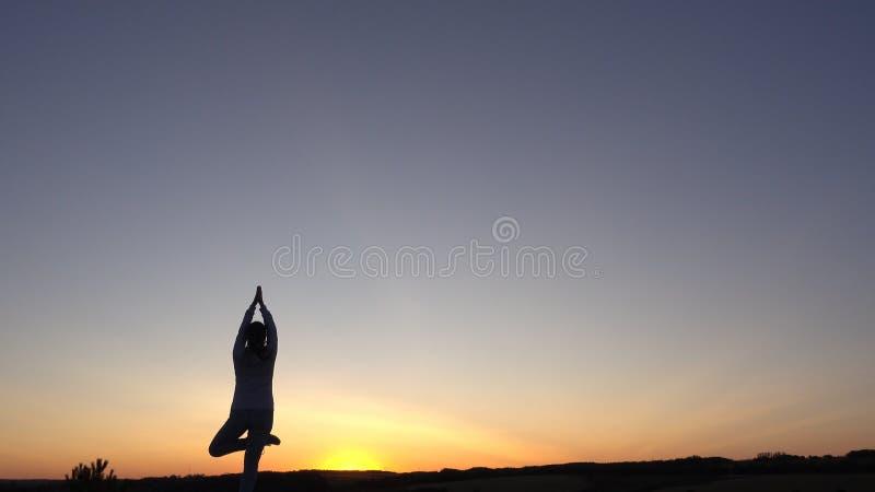 现出轮廓少妇实践的瑜伽和凝思在日落 库存图片