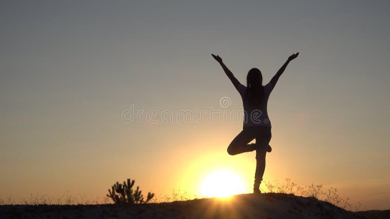 现出轮廓少妇实践的瑜伽和凝思在日落 免版税图库摄影