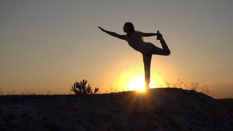 现出轮廓少妇实践的瑜伽和凝思在日落 免版税库存图片