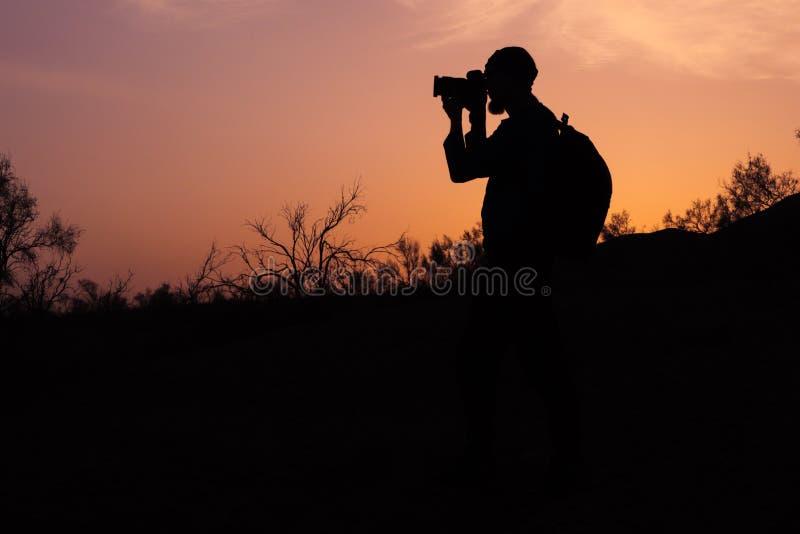 现出轮廓日落光beardedphotographer照相  免版税库存照片