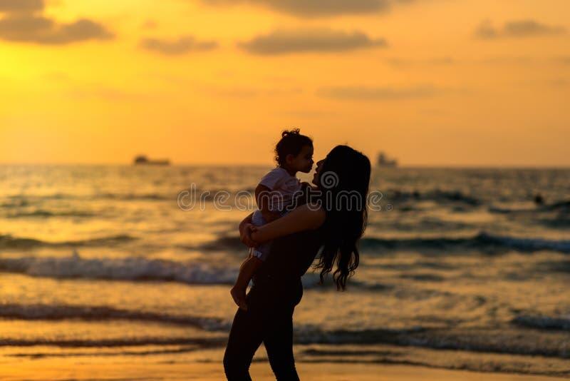 现出轮廓有使用和亲吻在海滩的女儿的年轻母亲在日落晚上天空背景 E 免版税库存图片