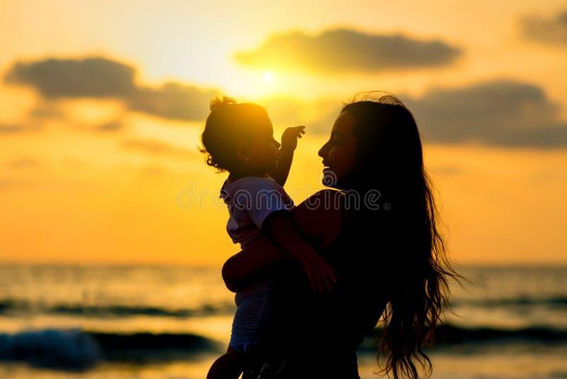 现出轮廓有使用和微笑在海滩的女儿的年轻母亲对日落 幸福家庭和旅行概念 免版税库存图片