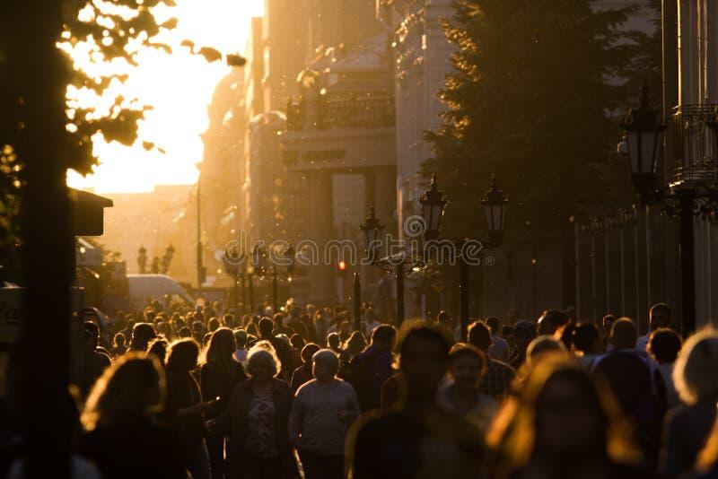 现出轮廓步行沿着向下步行区域的人人群在夏天晚上日落 免版税库存图片