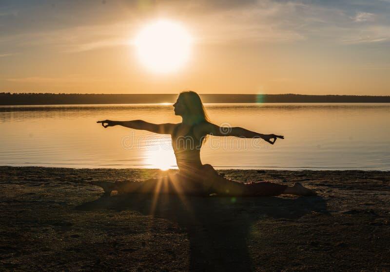 现出轮廓海滩的瑜伽妇女在日落. beautifuler, 安静.图片