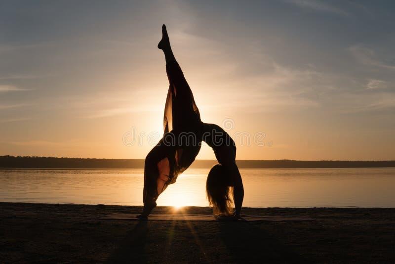 现出轮廓海滩的瑜伽妇女在日落. 本质, 火箭筒.图片