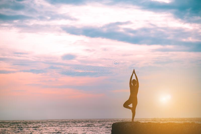 现出轮廓瑜伽妇女实践在类锻炼的海滩放松 免版税库存照片