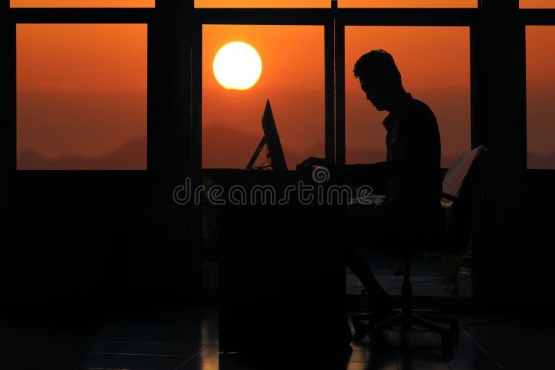现出轮廓研究有日落的一台计算机的商人 库存照片