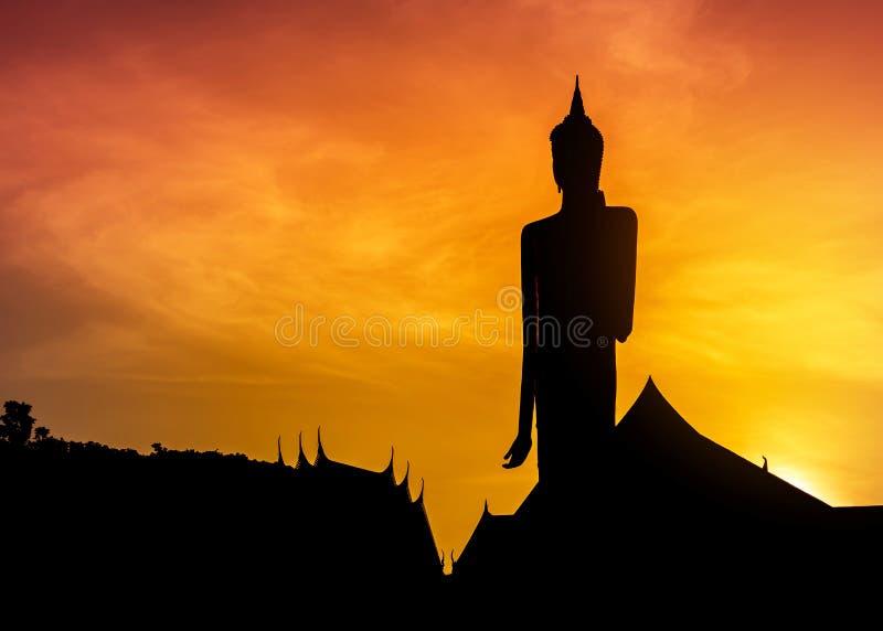 现出轮廓站立在日落的泰国寺庙的大菩萨雕象 库存照片