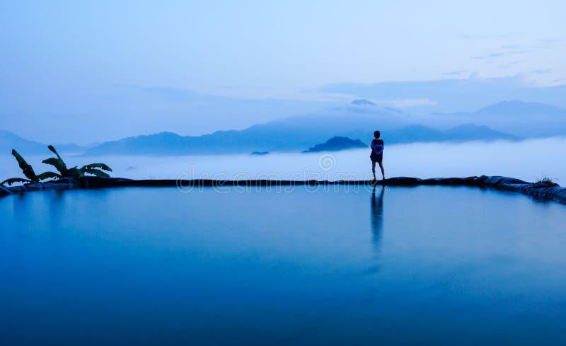 现出轮廓站立在蓝天和山惊人的风景的水池附近的少妇背面图在早晨雾 免版税库存照片