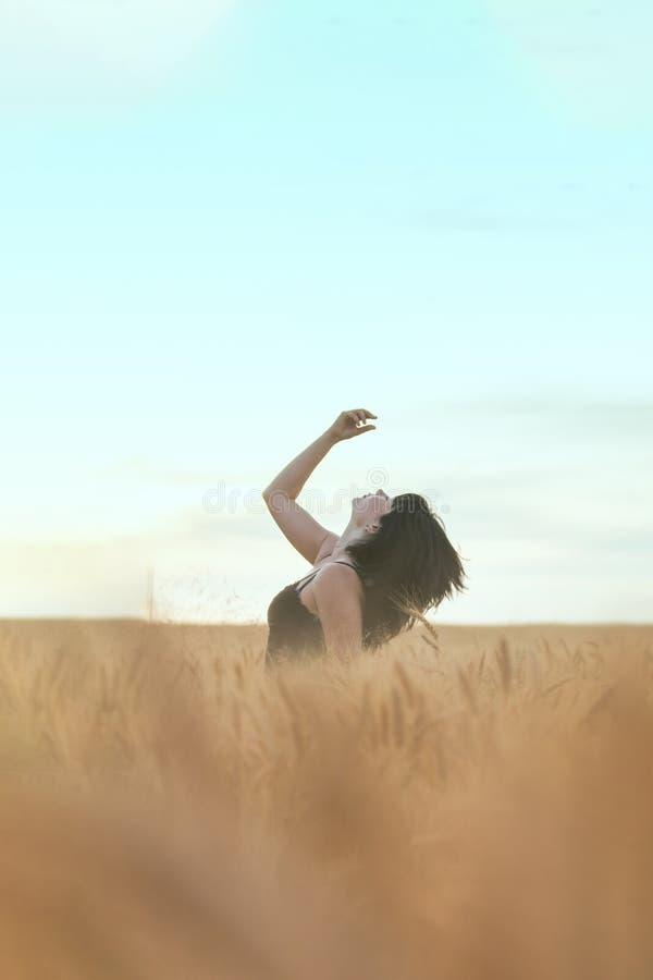 现出轮廓逗人喜爱的愉快的美丽的女性反对麦田背景在日落时 免版税库存图片