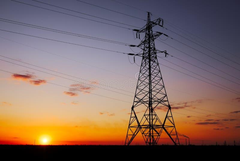 现出轮廓高压电塔在日落时间 高压输电线 r 免版税库存图片