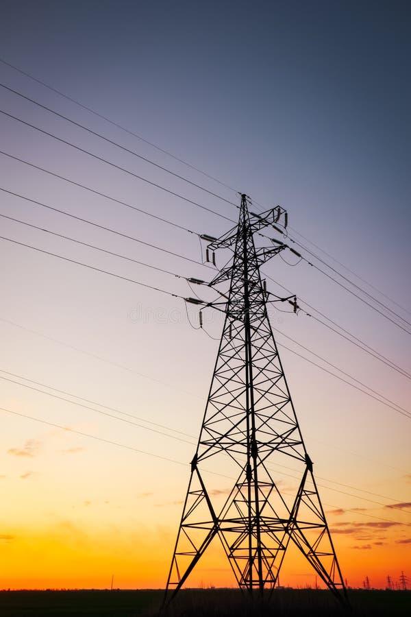 现出轮廓高压电塔在日落时间 高压输电线 r 免版税库存照片