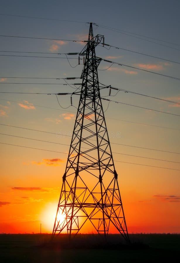 现出轮廓高压电塔在日落时间 高压输电线 r 免版税图库摄影