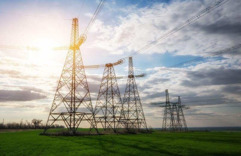 现出轮廓高压电塔 高压输电线 r 免版税库存照片