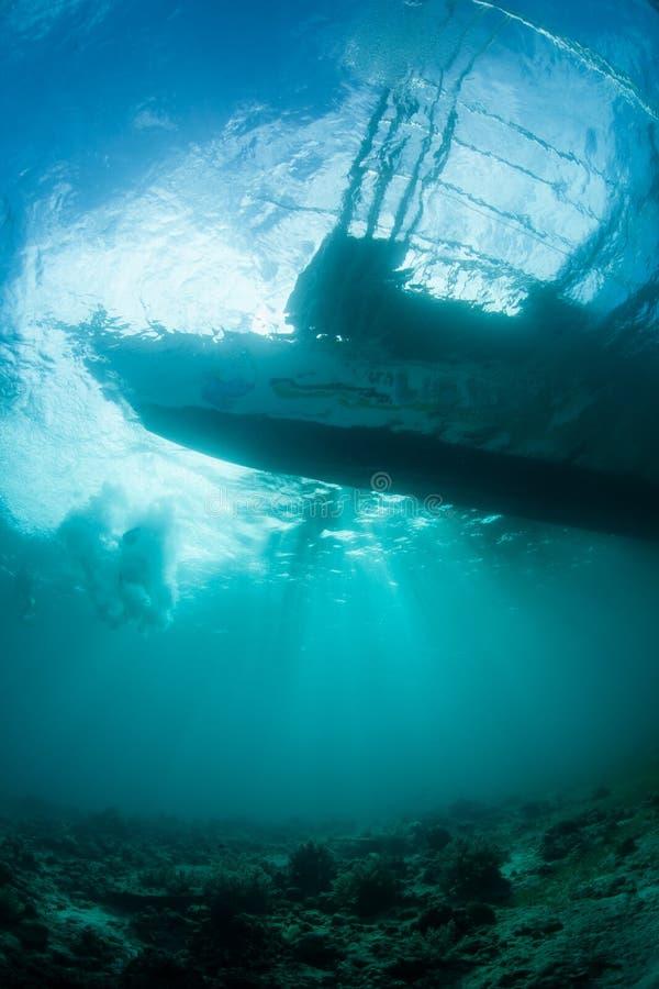 现出轮廓下潜小船的阳光 免版税库存图片