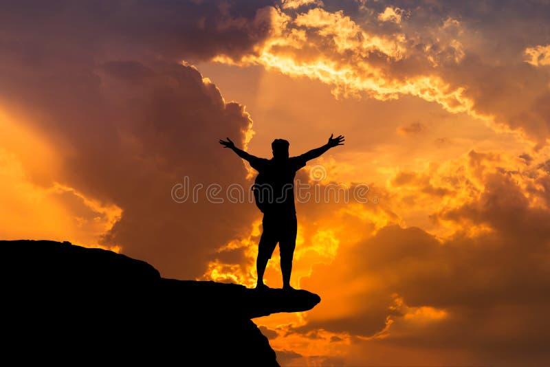 现出轮廓人背包徒步旅行者身分被上升成功胳膊的成就并且庆祝成功在山顶部 库存照片
