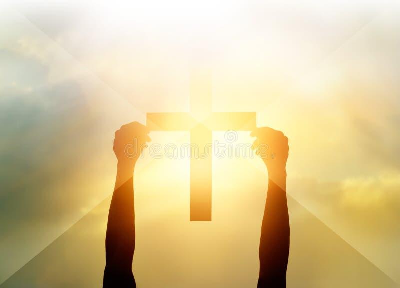 现出轮廓十字架在手上,在光的宗教标志和风景 免版税库存图片