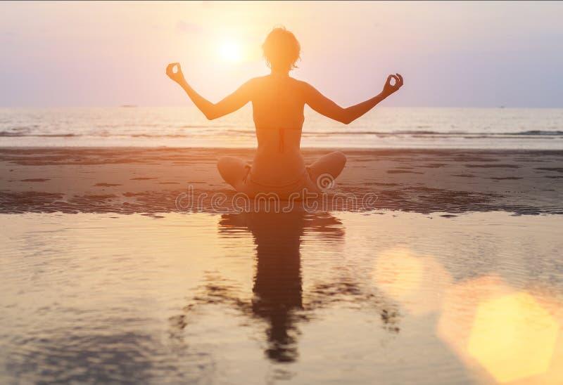 现出轮廓在海洋海滩的女子实践的瑜伽在超现实主义的日落 库存照片