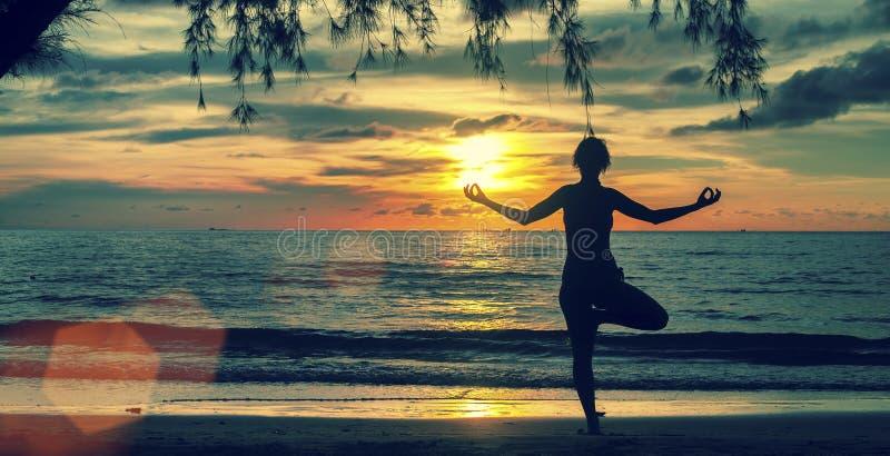 现出轮廓在海滩的女子实践的瑜伽在超现实主义的日落 图库摄影