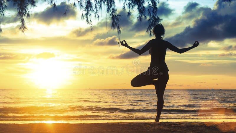 现出轮廓在海滩的女性实践的瑜伽在壮观的日落 免版税库存图片