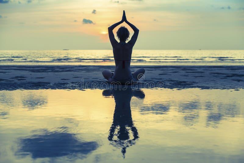 现出轮廓在海滩的少妇实践的瑜伽在超现实主义的日落 库存照片