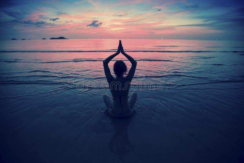 现出轮廓在海滩的少妇实践的瑜伽在超现实主义的日落 免版税库存图片