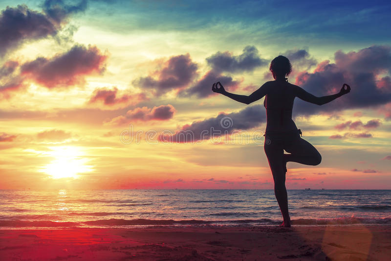 现出轮廓在海滩的少妇实践的瑜伽在超现实主义的日落 免版税库存照片