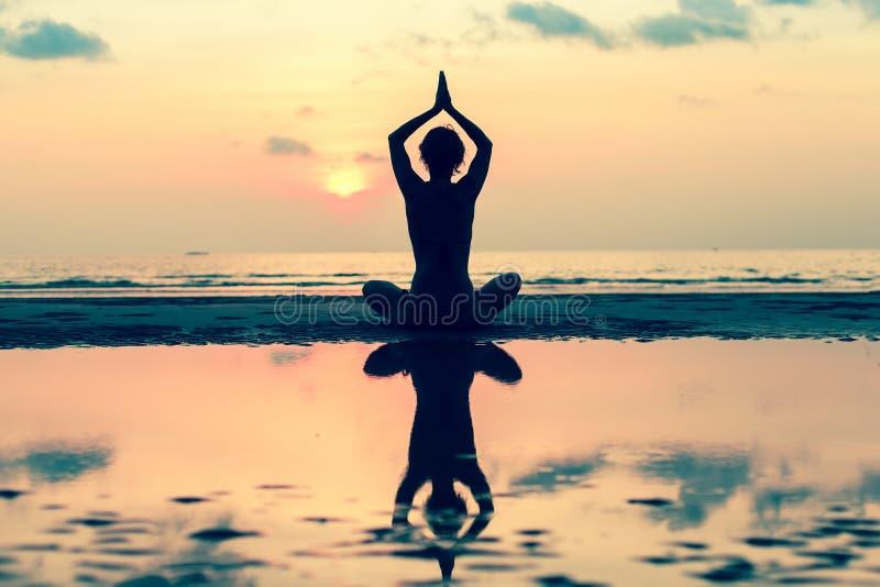 现出轮廓在海滩的少妇实践的瑜伽 免版税库存照片图片