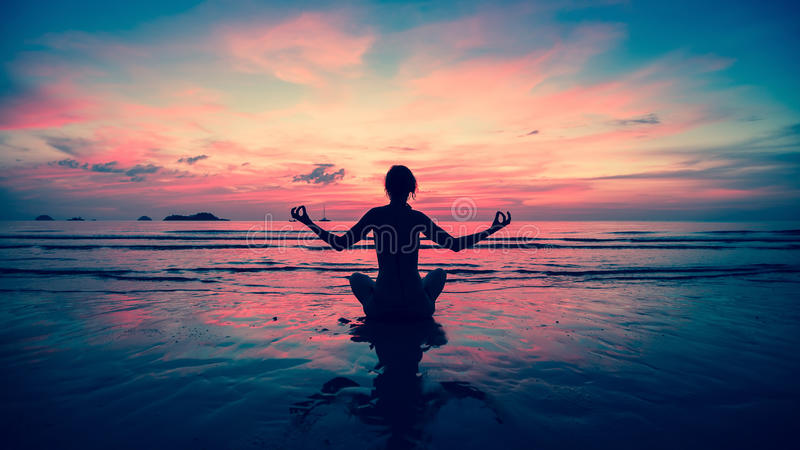 现出轮廓在海滩的少妇实践的瑜伽图片