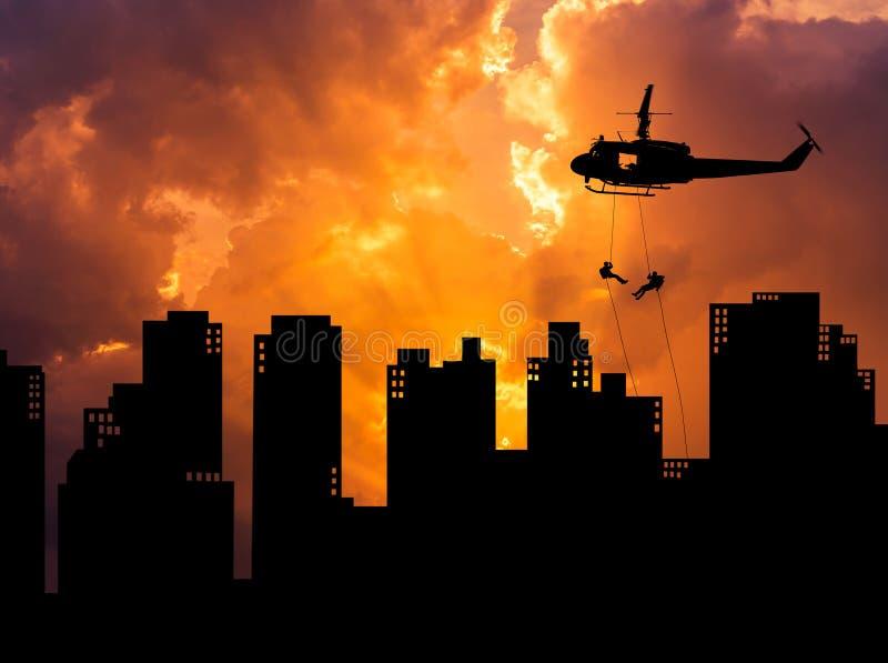 现出轮廓坐式下降法下来从在大厦摩天大楼的直升机的战士日落的 库存图片