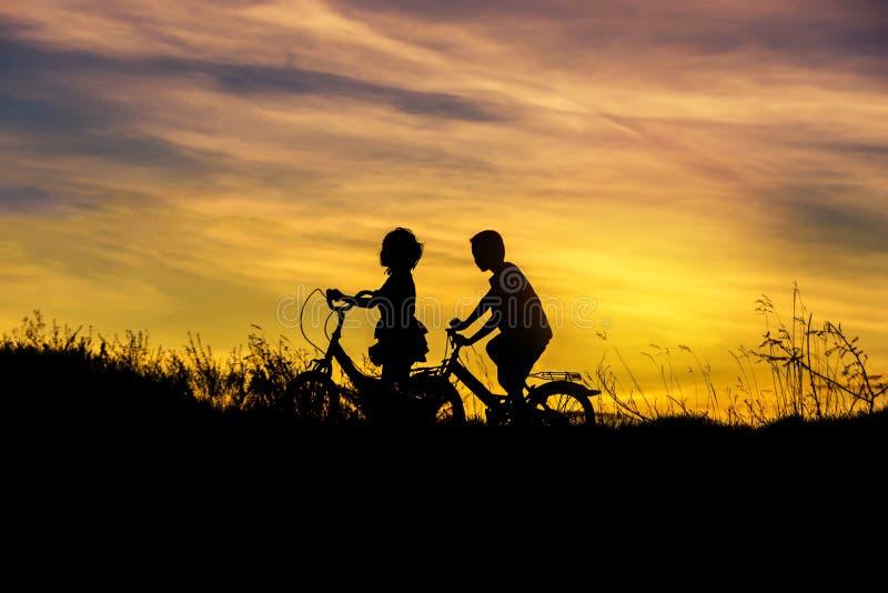 小女孩和小男孩_现出轮廓小男孩和小女孩在日落的骑马自行车. 少许, 愉快.
