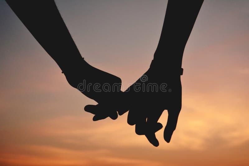 现出轮廓恋人的妇女和人在天空日落,概念VA 图库摄影