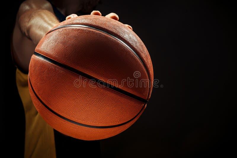 现出轮廓拿着在黑背景的观点的蓝球运动员篮子球 免版税库存照片