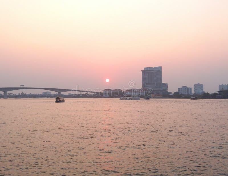 现出轮廓日落,在河城市视图的软的焦点与小船航行 库存图片