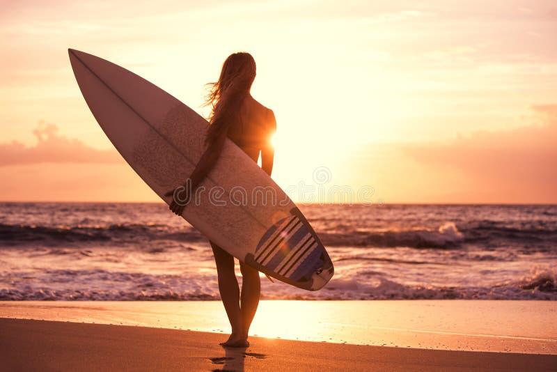 现出轮廓海滩的冲浪者女孩在日落 图库摄影