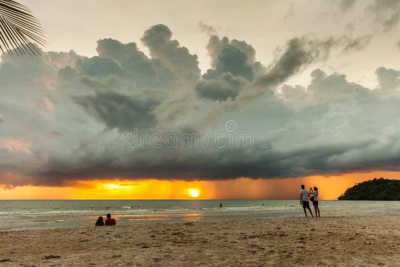 现出轮廓热带海滩的妇女在背景剧烈的风暴天空 库存照片