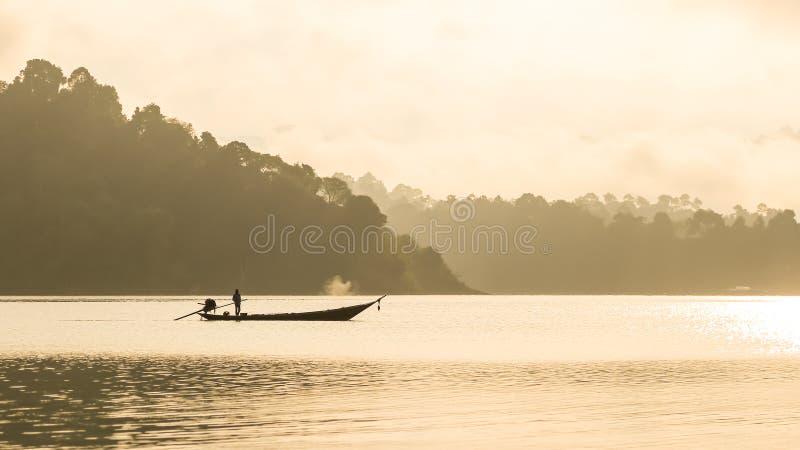 现出轮廓的渔夫和小船有山背景 免版税图库摄影
