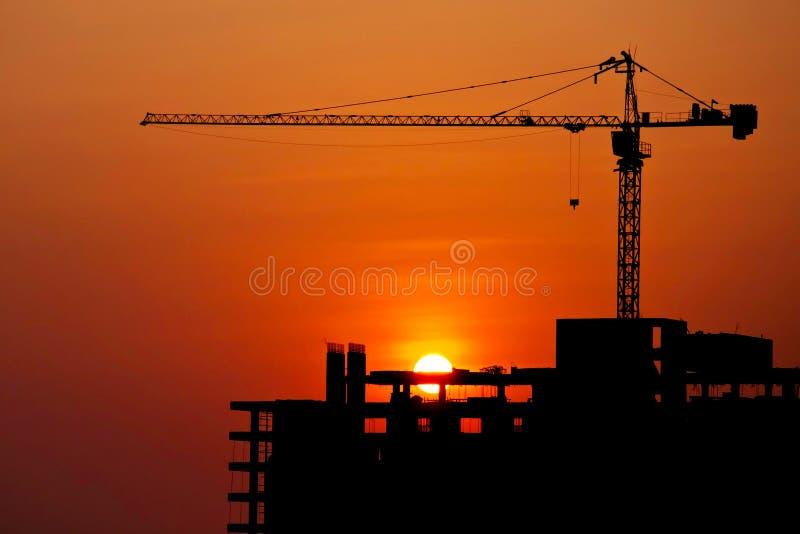 现出轮廓的建筑用起重机和大厦在建造场所 免版税库存照片