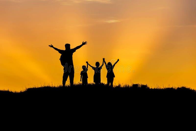 现出轮廓站立被举的手在日落的父亲和孩子 免版税库存照片