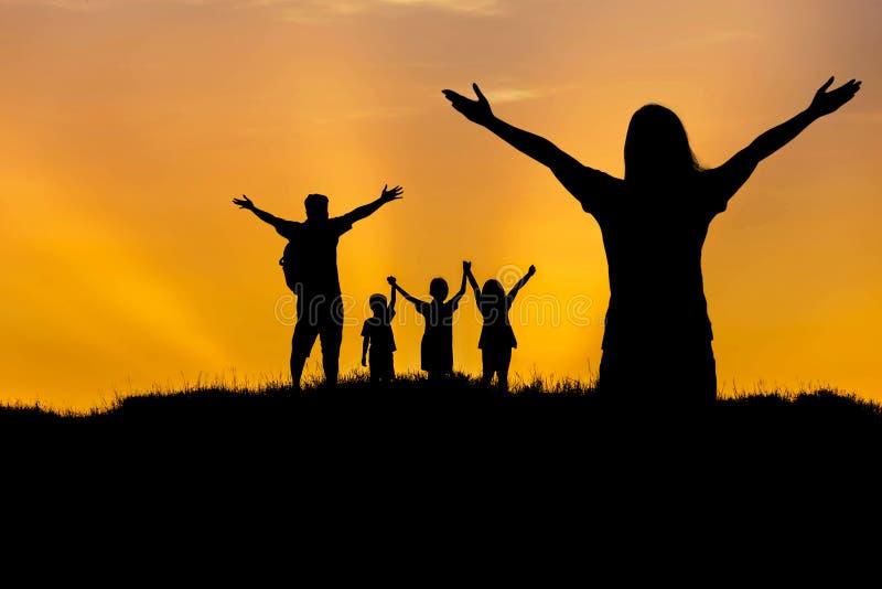 现出轮廓站立被举的手在日落的父母和孩子 免版税库存图片