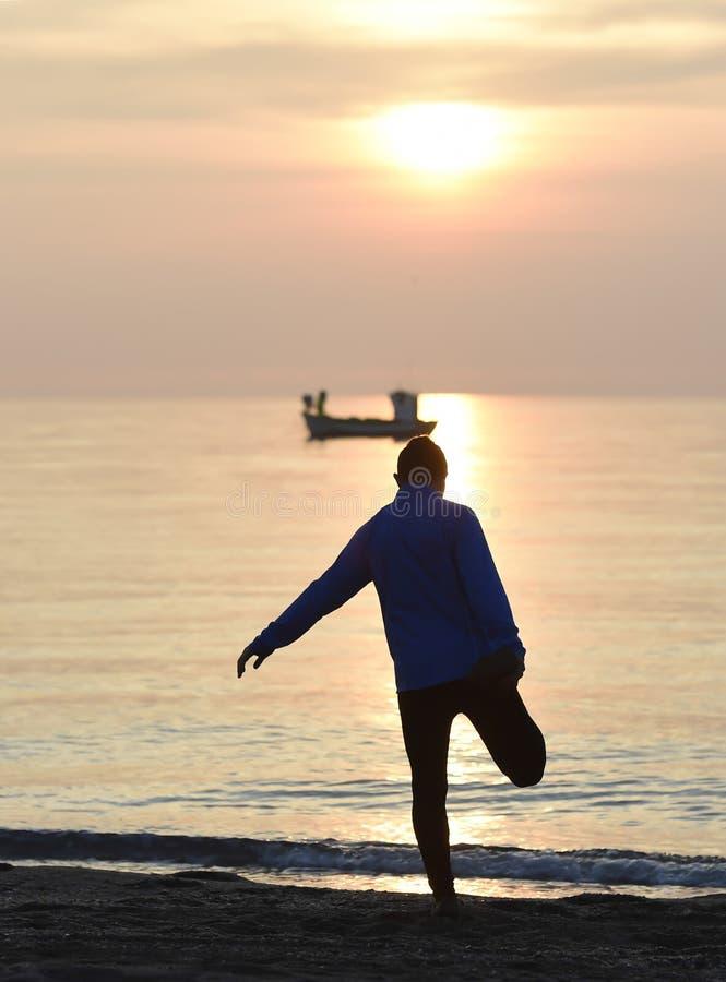 现出轮廓舒展腿的年轻体育人在连续锻炼以后户外在海滩在日落 免版税库存图片