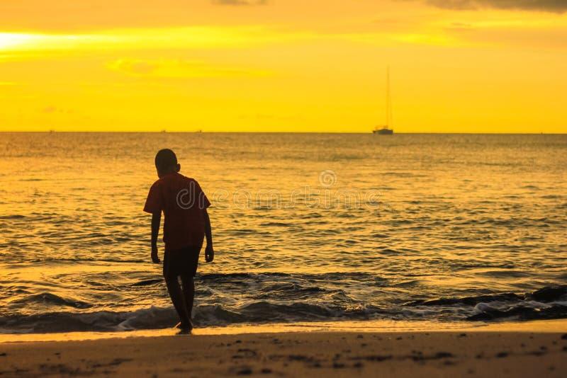 现出轮廓走入海的海滩男孩 免版税图库摄影