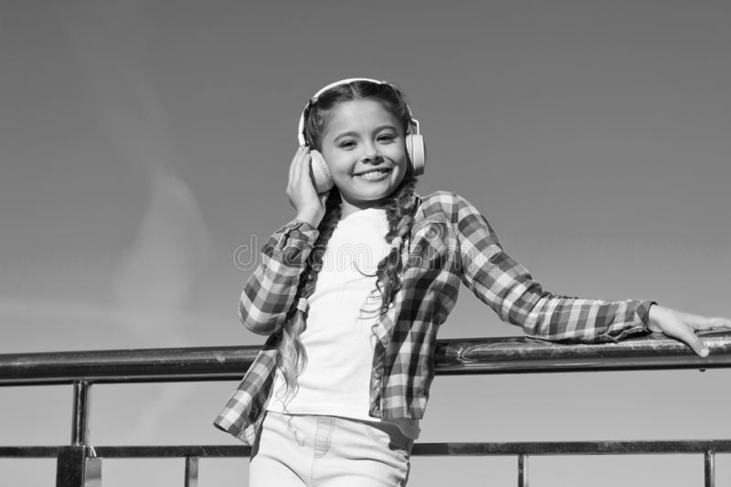 现在使您的孩子满意对可利用最佳的额定的孩子的耳机 女孩孩子听音乐户外与现代 免版税库存照片