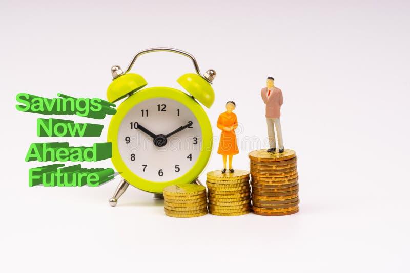 现在储款未来题字书面的,闹钟、硬币和前面商人缩样 图库摄影