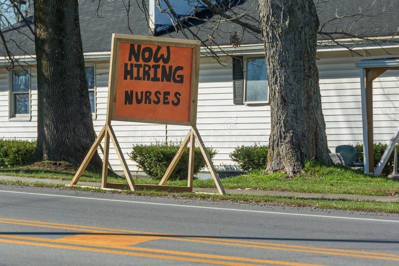 现在聘用的护士护理在一个地方老人院前面的标志 库存图片