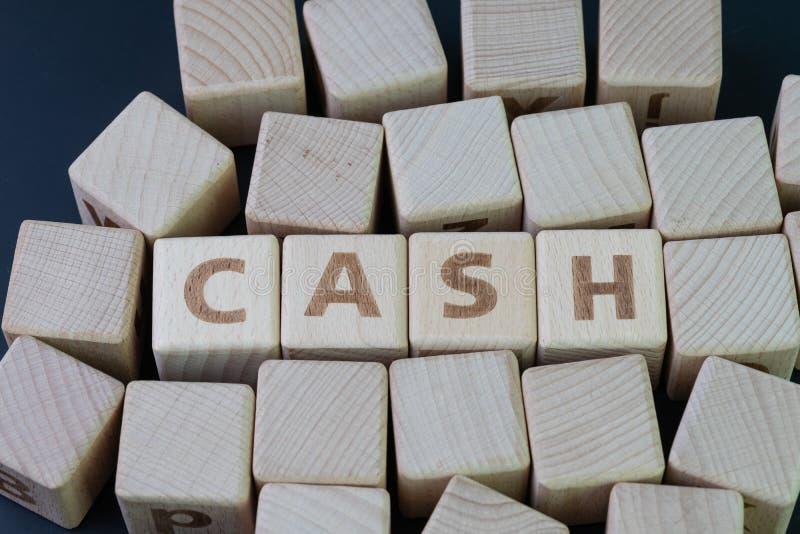现金、金钱或者支付任何东西概念的财富财产,与建立词现金的字母表的立方体木块在中心  免版税库存照片