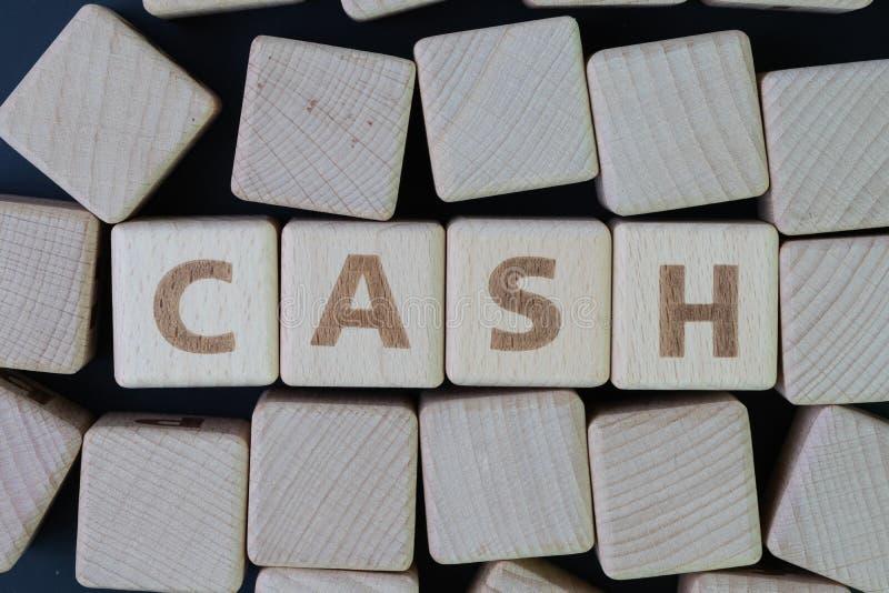 现金、金钱或者支付任何东西概念的财富财产,与建立词现金的字母表的立方体木块在中心  库存照片