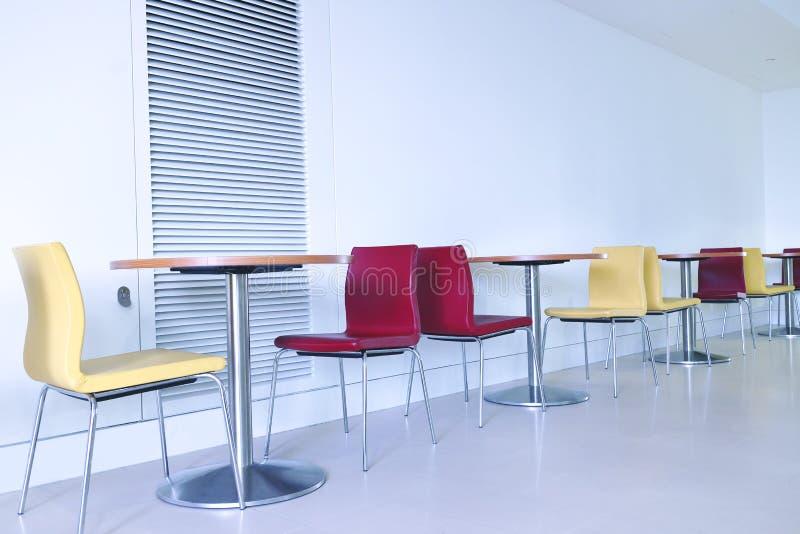 现代五颜六色的椅子和桌在自助食堂 免版税库存照片
