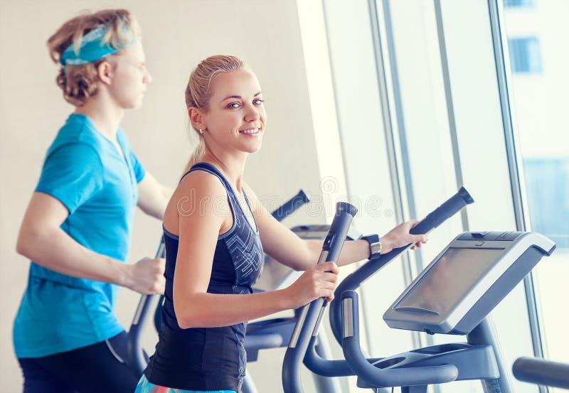 现代健身房的青年人在奔跑模拟器 免版税图库摄影